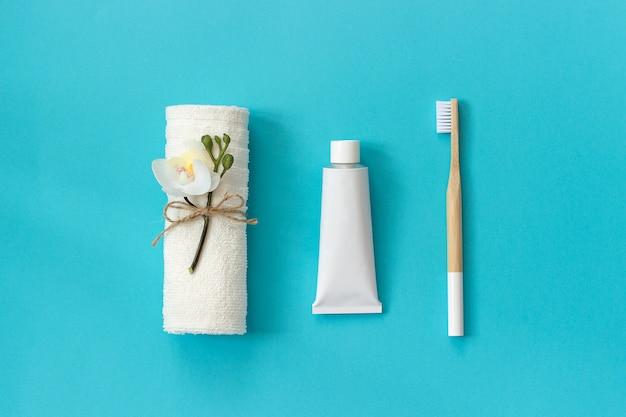 Natürliche umweltfreundliche bambusbürste mit weißen borsten, weißem tuch und zahnpastatube. zum waschen einstellen Premium Fotos
