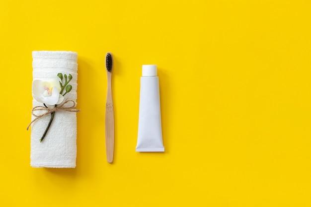 Natürliche umweltfreundliche bambusbürste, weißes handtuch und zahnpastatube. zum waschen einstellen Premium Fotos