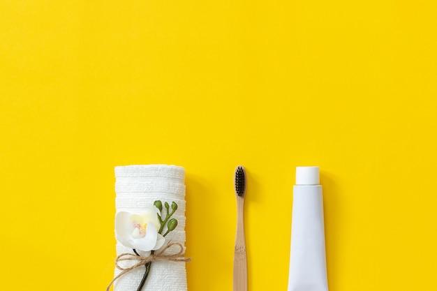 Natürliche umweltfreundliche bambusbürste, weißes handtuch und zahnpastatube Premium Fotos