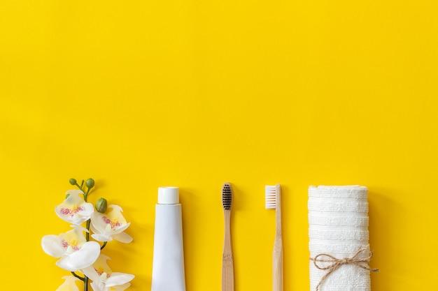 Natürliche umweltfreundliche bambusbürsten, handtuch und zahnpastatube Premium Fotos