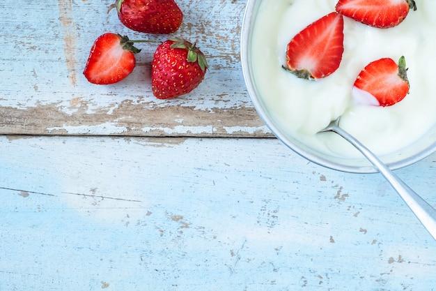 Natürlicher joghurt und erdbeerfrucht auf dem hölzernen hintergrund Premium Fotos