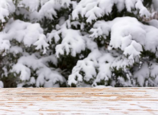 Natürlicher unscharfer winterhintergrund des weihnachtsneuen jahres mit einem holztisch und einem montagebereich für die platzierung von gegenständen. mock-up für text, glückwünsche, phrasen, schriftzüge Premium Fotos