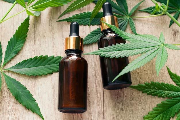 Natürliches ätherisches kräuterhanföl in einer glasflasche und in marihuanagrünblättern Premium Fotos
