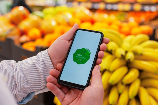 Natürliches produkt. ein mann hält ein smartphone in den händen Premium Fotos