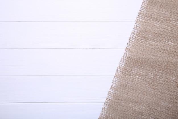 Natürliches sackleinen auf einem weißen hölzernen hintergrund. Premium Fotos