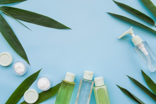 Natürliches schönheitsprodukt verziert mit blättern auf blauem hintergrund Kostenlose Fotos