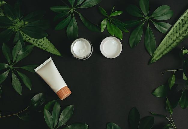 Naturkosmetik und grüne blätter auf schwarzem tisch. Premium Fotos