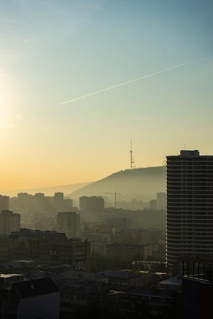 Nebelhafter herbstlicher sonnenaufgang über tiflis Premium Fotos
