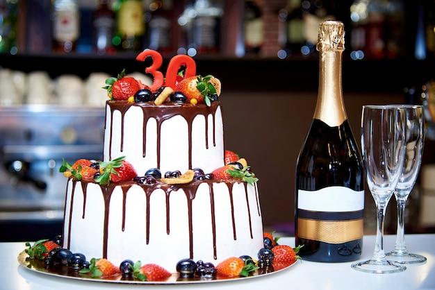 Neben einer flasche champagner steht ein zweistufiger weißer kuchen mit frischem obst und schokolade Premium Fotos