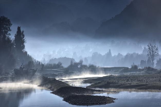 Nebliges ufer eines sees mit wäldern in der nacht Kostenlose Fotos