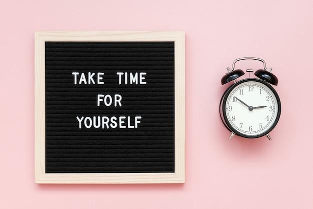 Nehmen sie sich zeit für sich. motivzitat auf briefkarton und schwarzem wecker Premium Fotos