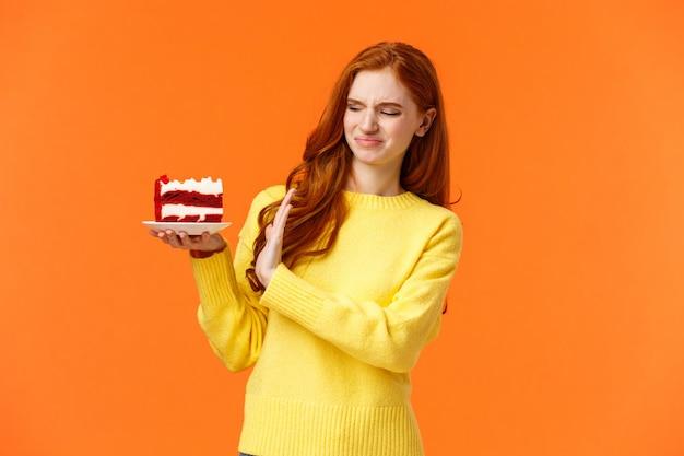 Nein danke, will nicht. nettes rothaariges mädchen, das versucht, versuchung zu widerstehen, beißen sie köstliche süßigkeiten, halten sie leckeren kuchen und zeigen sie stopp, ablehnung oder ablehnung mit verzogenem gesicht, drücken sie abneigung aus, abneigung Premium Fotos
