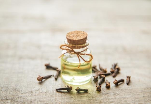 Nelkenöl in einer kleinen flasche. tiefenschärfe. Premium Fotos