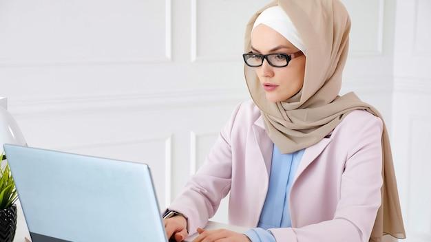Nerd muslimische frau in beige hijab und anzug arbeitet an einem bachelor-abschlussprojekt, das auf laptop schreibt Premium Fotos
