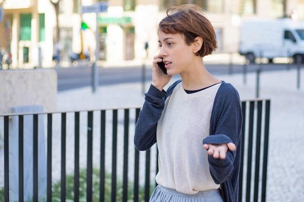 Nervöse frau, die auf smartphone geht und spricht Kostenlose Fotos
