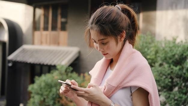 Nette asiatische wandererbloggerfrau, die smartphone nach richtung verwendet und auf standortkarte beim reisen nach chinatown in peking, china betrachtet. Kostenlose Fotos