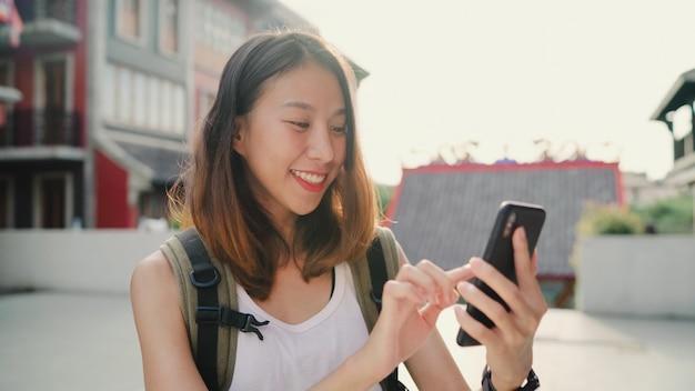 Nette asiatische wandererbloggerfrau, die smartphone nach richtung verwendet und auf standortkarte schaut Kostenlose Fotos