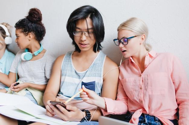 Nette blonde frau in den gläsern, die mit bleistift auf den bildschirm des telefons zeigen, während musik mit asiatischem kerl hört. fröhliche studenten, die zusammen lernen und spaß am college haben. Kostenlose Fotos