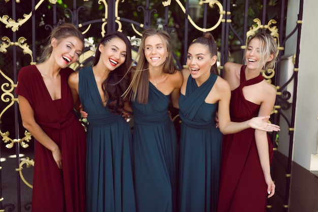 Nette brautjungfern in den erstaunlichen roten und grünen kleidern, die nahe den toren, partei, hochzeit, spaß, frisur, jung, lustig, make-up, ereignis, lächelnd, lachend aufwerfen Kostenlose Fotos