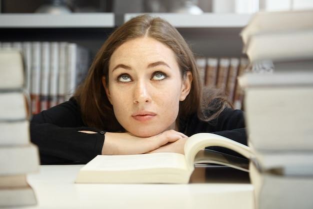 Nette brünette studentin in schwarzer jacke, die lehrbuch oder handbuch in der universitätsbibliothek studiert und liest, aber schwierigkeiten hat, material zu verstehen, die augen zu verdrehen, gelangweilt und verwirrt auszusehen Kostenlose Fotos