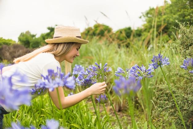 Nette dame im hut nahe blauer blüte im park Kostenlose Fotos