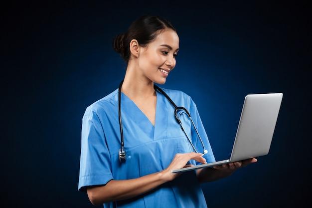 Nette dame in der medizinischen uniform unter verwendung des laptops Kostenlose Fotos