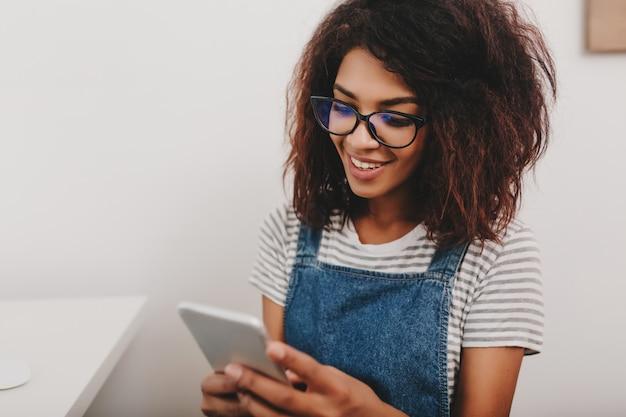 Nette dame mit bronzehaut, die neue nachrichten in den sozialen netzwerken mit ihrem telefon prüft Kostenlose Fotos