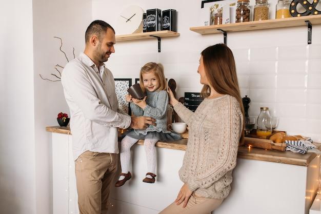 Nette eltern und ihr nettes tochtermädchen in der küche zu hause. Premium Fotos