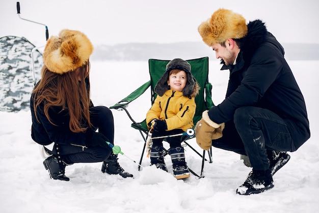 Nette familie, die auf einem winterfischen mit kleinem sohn sitzt Kostenlose Fotos