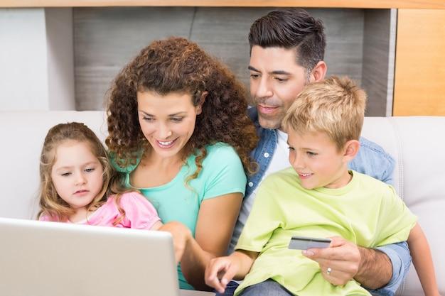 Nette familie, die auf sofa mit dem laptop online kauft sitzt Premium Fotos