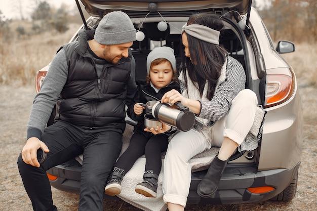 Nette familie, die ein heißes getränk in einem winterfeld nimmt Kostenlose Fotos