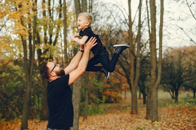 Nette familie, die in einem herbstpark spielt Kostenlose Fotos