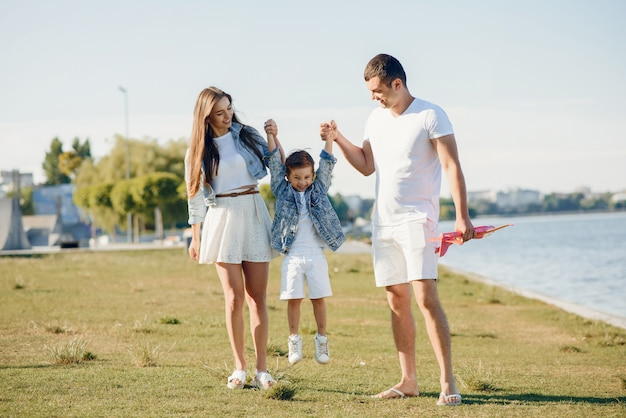 Nette familie, die in einem sommerpark spielt Kostenlose Fotos