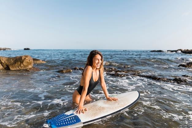 Nette frau, die auf surfbrett nahe ufer sich lehnt Kostenlose Fotos
