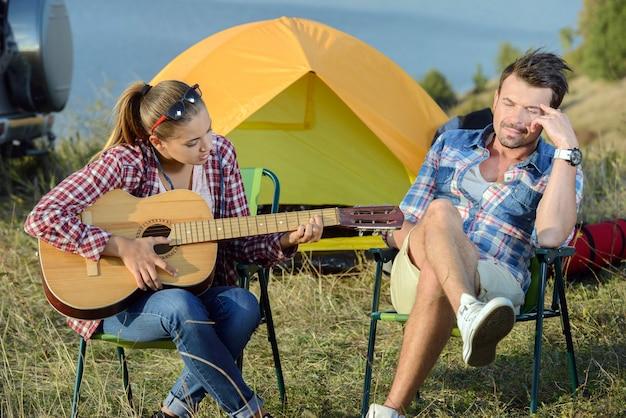 Nette frau, die ihrem mann auf kampierender reise ein ständchen bringt. Premium Fotos