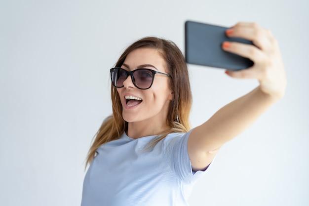 Nette frau, die selfie foto auf smartphone macht Kostenlose Fotos