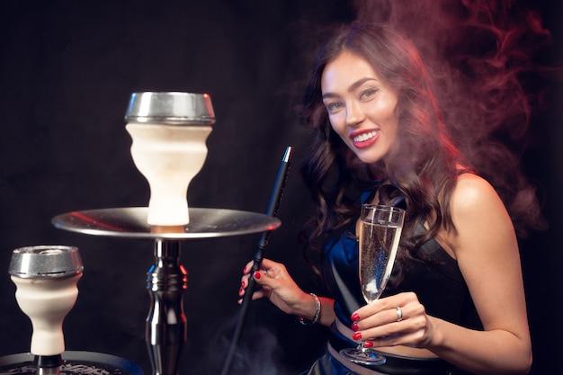 Nette frau, die shisha raucht und cocktail in einer bar trinkt Premium Fotos