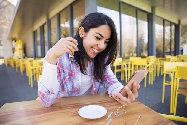 Nette frau, die smartphone verwendet und kaffee im café trinkt Kostenlose Fotos