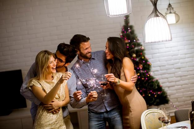 Nette frauen und männer, die zu hause silvester mit scheinen und wein feiern Premium Fotos