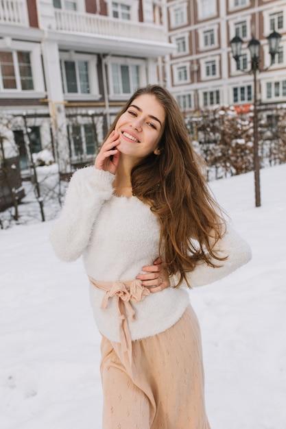 Nette freudige erstaunliche junge frau mit langen brünetten haaren im weißen wollpullover, leichter rock, der auf straße auf winterzeit geht. fröhliche stimmung, positive wahre gefühle, schnee. Kostenlose Fotos