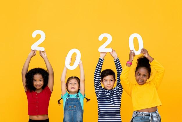 Nette gemischte rassenkinder, die lächeln und 2020 zahlen halten Premium Fotos