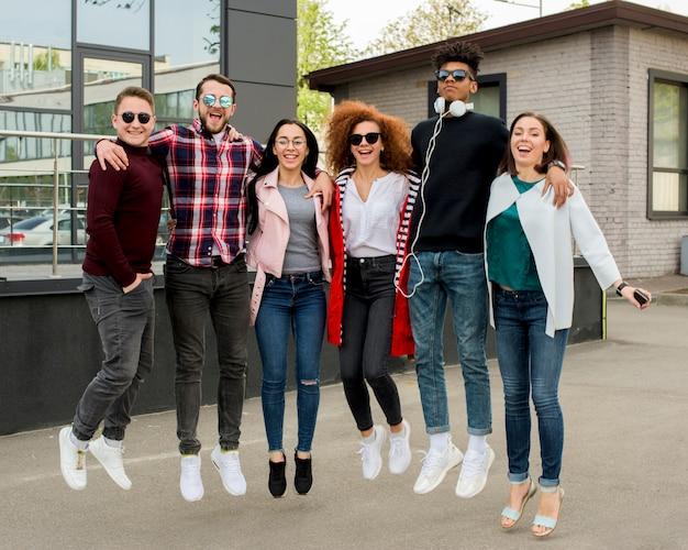 Nette gemischtrassige gruppe von personen, die zusammen auf straße springt Kostenlose Fotos