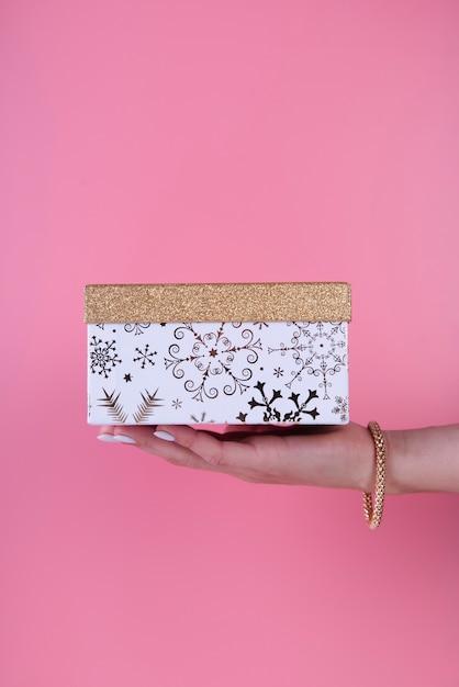 Nette geschenkbox in der hand gehalten auf rosa hintergrund Kostenlose Fotos