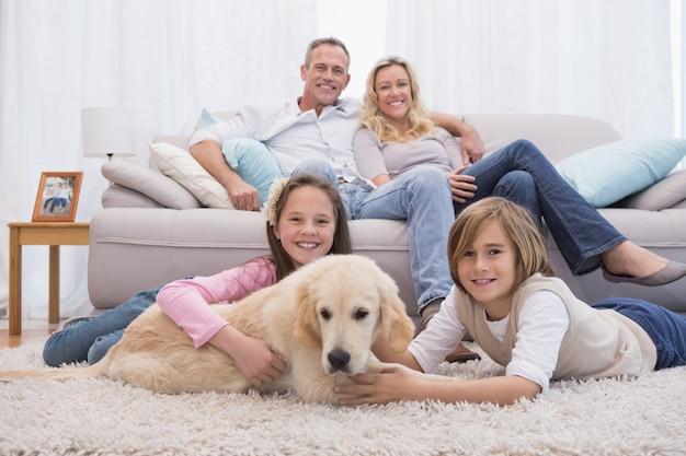 Nette geschwister, die mit hund mit ihrem elternteil auf dem sofa spielen Premium Fotos