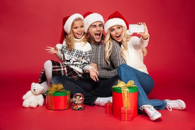 Nette glückliche junge familie, die weihnachtshüte trägt, machen selfie Kostenlose Fotos