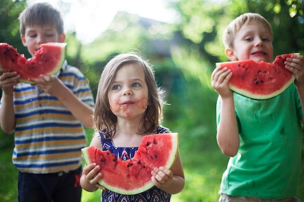 Nette glückliche kinder essen wassermelone im garten Premium Fotos