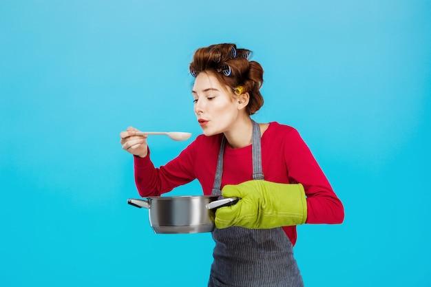 Nette hausfrau riecht und schmeckt heiße hausgemachte suppe in der küche Kostenlose Fotos