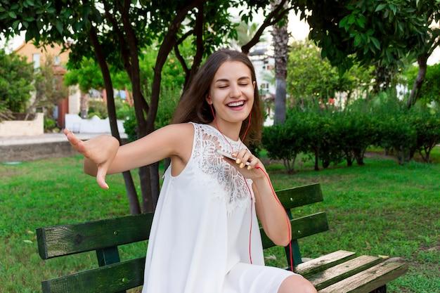 Nette herrliche frau hört musik in den kopfhörern und tanzt auf die bank im park an einem warmen tag Premium Fotos