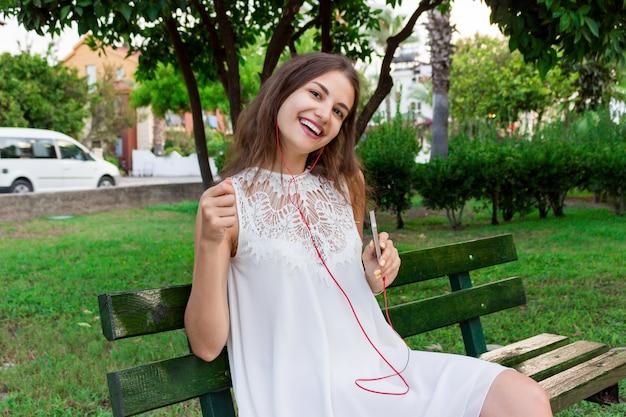 Nette herrliche frau hört musik in den kopfhörern und tanzt auf die bank in den park an einem warmen tag Premium Fotos