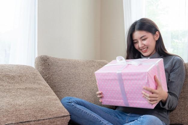 Nette jugendfrau, die glücklich sich fühlt und die rosa geschenkbox anwesend auf couch umarmt Kostenlose Fotos